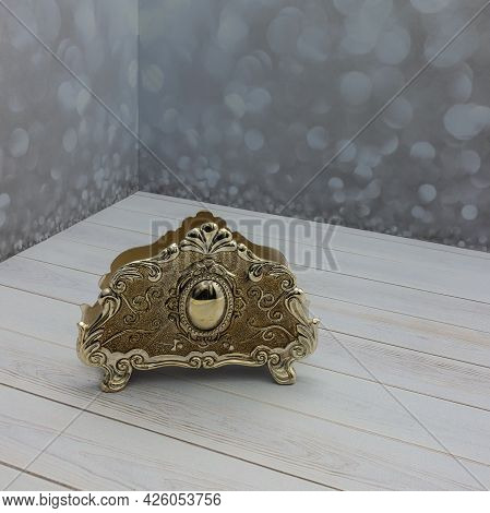 A Gold-colored Metal Napkin Holder Stands On A Plank Surface. Decorated With Patterns And Ornaments.