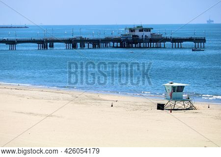 July 6, 2021 In Long Beach, Ca:  Lifeguard Station On A Sandy Beach Overlooking A Rustic Wooden Pier