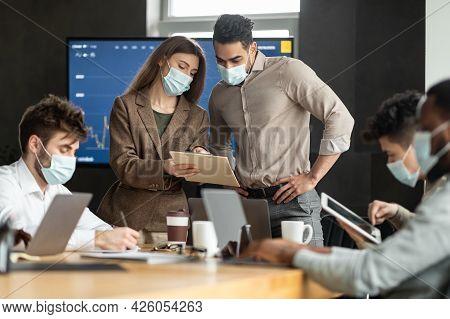Coworkers Having Brainstorm Meeting In Boardroom, Woman Showing Documenation