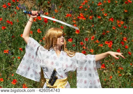 Young Asian Woman In Traditional Kimono Trains Fighting Techniques With Katana Sword