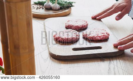 Cropped View Of Chef Near Formed Mince Patty On Chopping Board