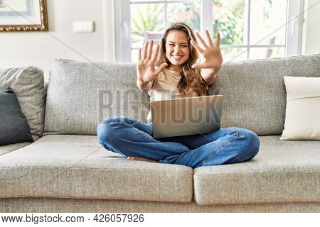 Beautiful young brunette woman sitting on the sofa using computer laptop at home showing and pointing up with fingers number ten while smiling confident and happy.
