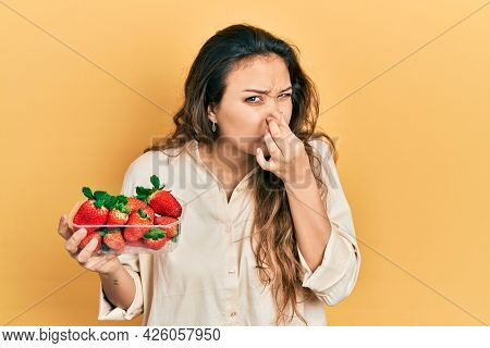 Young hispanic girl holding strawberries smelling something stinky and disgusting, intolerable smell, holding breath with fingers on nose. bad smell