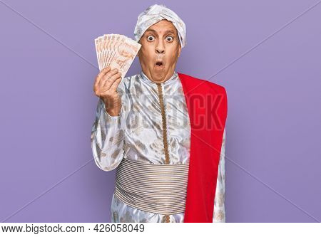 Senior hispanic man wearing sherwani costume holding 50 indian rupee banknotes scared and amazed with open mouth for surprise, disbelief face