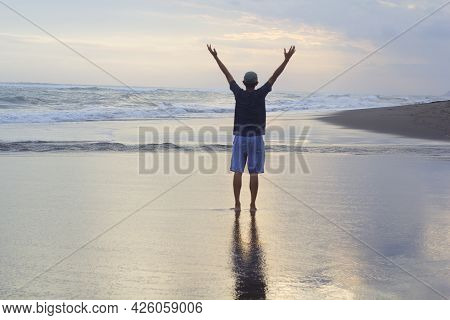 Man Standing Alone On The Beach, With Arm Raised Against The Sea At Sunset. Freedom And Self Healing