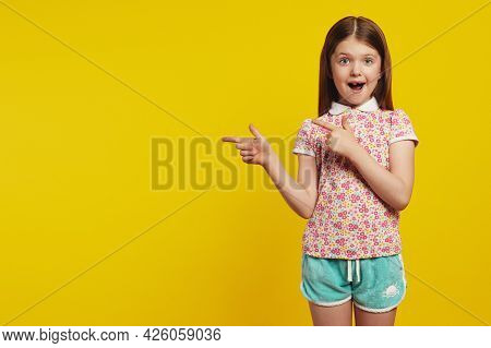 Horizontal Shot Amazed Caucasian Girl Kid, Points Away With Both Forefingers, Shows Blank Space For