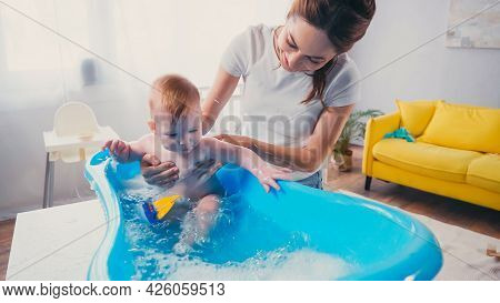 Happy Mother Supporting Infant Son Playing With Toy While Taking Bath In Baby Bathtub