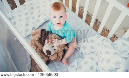 High Angle View Of Barefoot Infant Boy Playing In Teddy Bear In Baby Crib