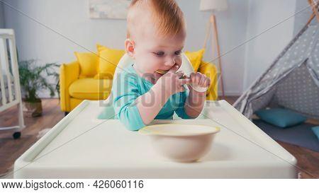 Infant Boy Sitting In Feeding Chair And Sucking Spoon Near Bowl