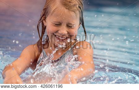 Portrait of a Little Smiling Girl Having Fun and Splashing in the Pool. Spending Summer Weekend in Aqua park. Happy Summer Holidays.