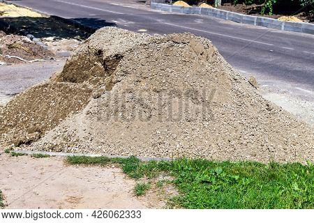 A Pile Of Sand-stone Mixture. Near Road. Asphalt. Grass. Green.
