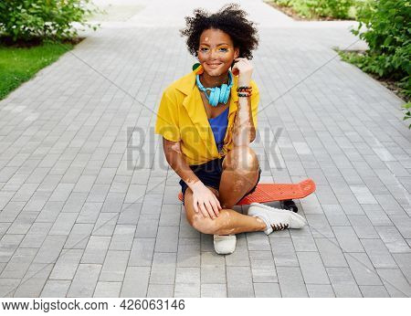 Positive Teenage Girl With Vitiligo Sitting On Red Skateboard Outdoor At City Park