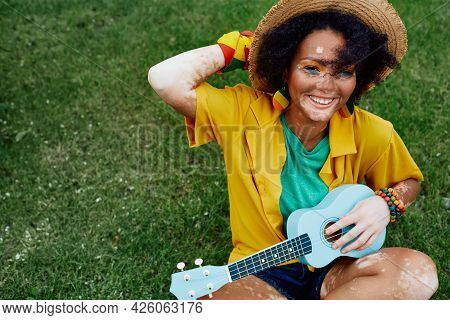 Playful African American Woman With Blue Ukulele Having Fun While Sitting On Green Lawn Wearing Colo