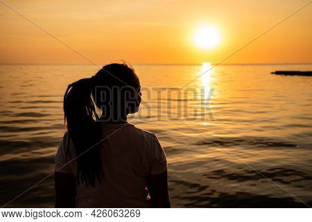 Woman Looking At The Sunset By The Sea. Silhouette Of A Dreamer Girl Looking Hopeful At The Horizon