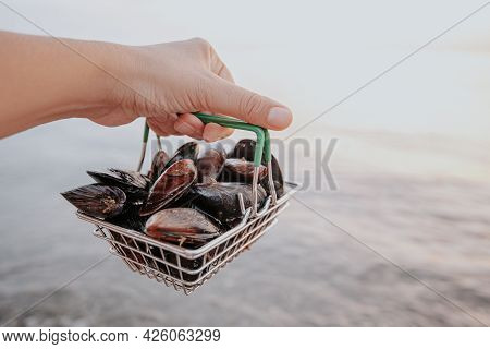 A Hand Holds A Certain Amount Of Fresh Raw Mussels In A Consumer Basket On The Seashore