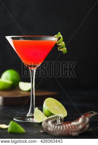 Cosmopolitan Cocktail In Classic Crystal Glass With Lime Peel And Fresh Limes With Strainer On Black