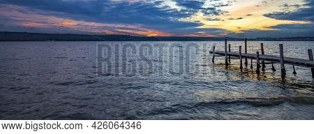Banner Of Idyllic View Lake Coast With Wooden Pier After Sunset