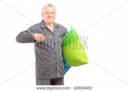 Mature man in pajamas holding a tooth brush and a pillow isolated on white background