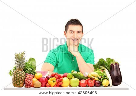 Young man posing with a pile of fruits and vegetables, isolated on white background