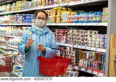 24.04.2021, Russia, Moscow. A Caucasian Woman In A Protective Mask Against Coronavirus Picks Dairy P
