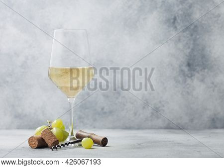 Glass Of Summer White Wine With Grapes, Corks And Corkscrew On Light Table Background.