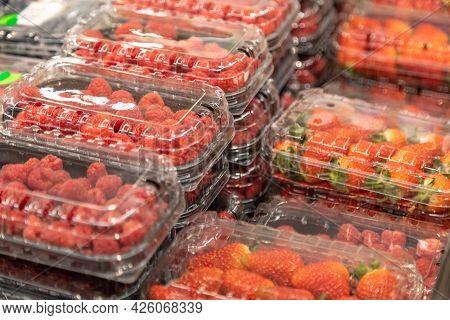 Fresh Juicy Beautiful Berries Of Strawberries And Raspberries In An Individual Plastic Package On Th