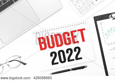 Text Budget 2022 On Card. Laptop, Glasses, Pen, Calculating Machine And Clipboard With Charts And Gr