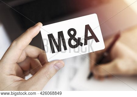 Merger And Acquisition Concept. Close Up Of Hand Business Person Keeps Card With Letters M And A. Do