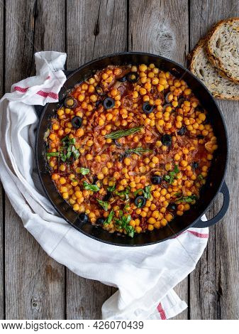 Baked Chickpea With Vegetables, Olives And Sun-dried Tomatoes In Iron Pan, Frying Pan On Wooden Tabl