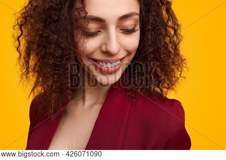 Optimistic Young Female In Trendy Jacket And With Curly Hair Smiling And Looking Down Against Yellow