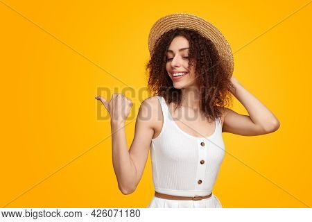 Optimistic Young Woman Touching Straw Hat And Pointing Away While Standing Against Yellow Background