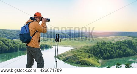 Man Hiker Taking Photo On Top Of Mountain At Sunset. Banner.