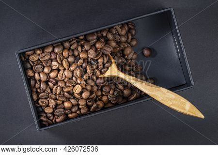 Roasted Coffee Beans In A Black Box With A Wooden Spoon, Top View