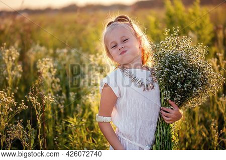 Happy Little Caucasian Girl 5 Years Old With A Bouquet Of Flowers Of Chamomiles In The Meadow Lookin