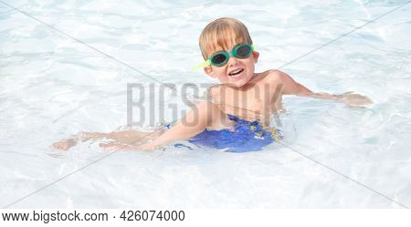 Smiling preschool boy wearing goggles in a pool