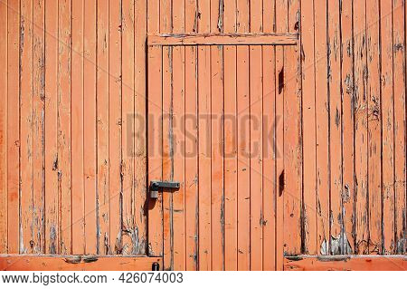 Weathered old orange wooden wall with door and lock