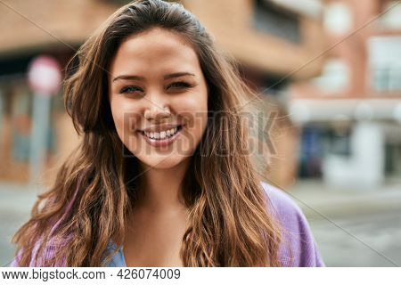 Young hispanic woman smiling happy standing at the city.