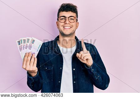 Young hispanic man holding egyptian pounds banknotes smiling with an idea or question pointing finger with happy face, number one