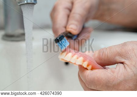 Asian Senior Or Elderly Old Woman Patient Use Toothbrush To Clean Partial Denture Of Replacement Tee