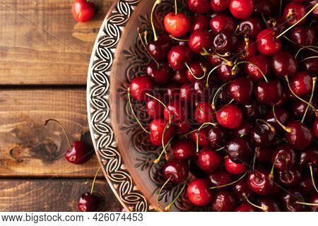 A Lot Of Ripe Cherries Are Lying On A Copper Tray With A Pattern.