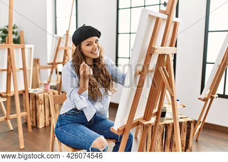 Young hispanic artist woman painting on canvas at art studio beckoning come here gesture with hand inviting welcoming happy and smiling