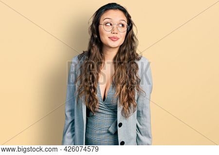 Young hispanic girl wearing business clothes and glasses smiling looking to the side and staring away thinking.