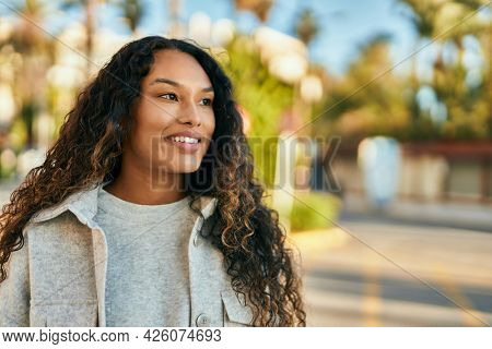 Young latin woman smiling happy standing at the city.