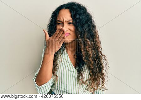 Young latin woman wearing casual clothes smelling something stinky and disgusting, intolerable smell, holding breath with fingers on nose. bad smell