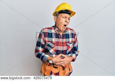 Senior hispanic man wearing handyman uniform with hand on stomach because indigestion, painful illness feeling unwell. ache concept.