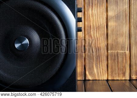 A Large Loud Subwoofer In A Wooden Case With A Metal Grille And Volume And Tone Controls Stands Agai