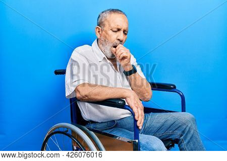 Handsome senior man with beard sitting on wheelchair feeling unwell and coughing as symptom for cold or bronchitis. health care concept.