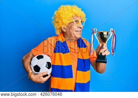 Senior hispanic man football hooligan cheering game holding ball and trophy smiling looking to the side and staring away thinking.