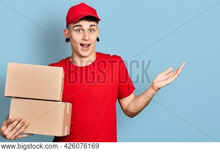 Young caucasian boy with ears dilation holding delivery package celebrating achievement with happy smile and winner expression with raised hand