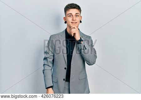 Young caucasian boy with ears dilation wearing business jacket looking confident at the camera smiling with crossed arms and hand raised on chin. thinking positive.